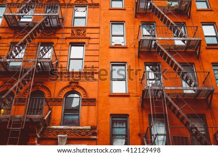 Escape fire ladders at beautiful colorful house facades in New York. Manhattan New York City - Background texture pattern of Buildings.  - stock photo