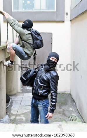 Escape from a robbery. One tries to climb on the rails. Second is on the lookout - stock photo