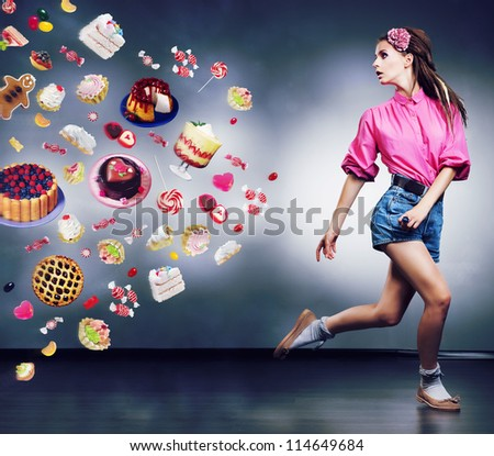 Escape. Resolute running woman refuses to eating tasty cakes and chocolate. Diet concept - stock photo