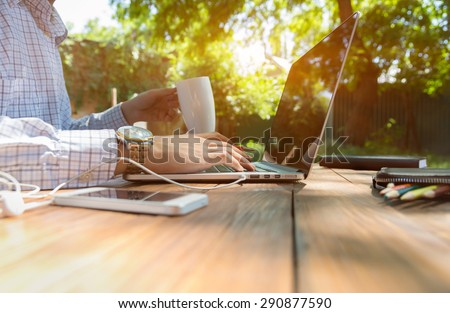 Escaped of office. Business style dressed man sitting at natural country style wooden desk with electronic gadgets around working on laptop drinking coffee sunlight and green terrace on background - stock photo