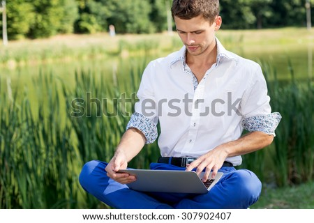 Escaped of office. Business style dressed man sitting in the park working on laptop and green terrace on background