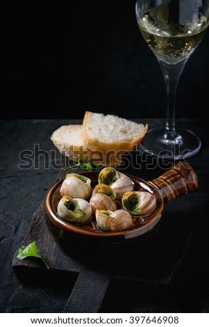 Escargots de Bourgogne - Snails with herbs butter, gourmet dish, in traditional ceramic pan with parsley, bread and glass of white wine on wooden chopping board over black textured background. - stock photo