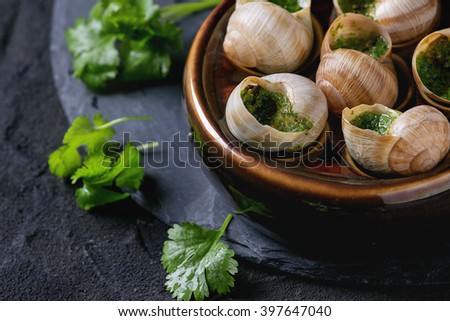 Escargots de Bourgogne - Snails with herbs butter, gourmet dish, in traditional ceramic pan with parsley and bread on stone slate board over black textured background. Close up - stock photo