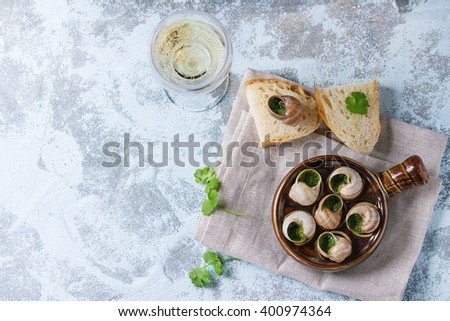Escargots de Bourgogne - Snails with herbs butter, in traditional ceramic pan with parsley, bread and glass of white wine on textile napkin over blue textured background. Top view, copy space
