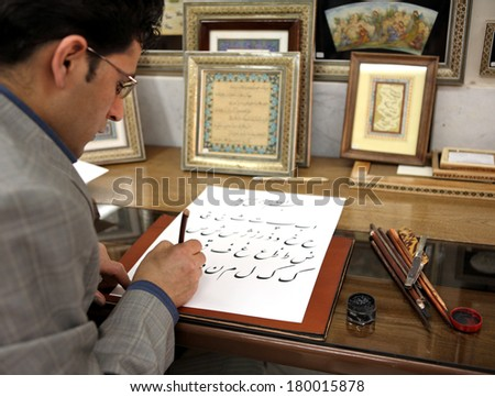 ESFAHAN, IRAN - DECEMBER 01, 2007:  Iranian calligraphy artist at work  traditional Persian art of decorative writing - stock photo