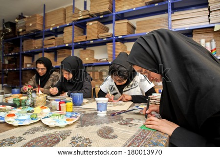ESFAHAN, IRAN - DECEMBER 01, 2007:  Muslim women artists in black headscarfs paint traditional Persian miniature - stock photo