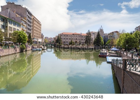 ESKISEHIR, TURKEY - APRIL 16, 2016 : View of Porsuk river flowing along the city in Eskisehir with trees and houses around on blue sky background.