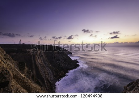 Espichel Cape cliffs surf and lighthouse at sunset, Setubal, Portugal - stock photo