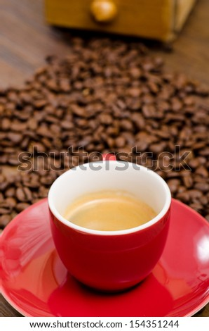 Espresso coffe in a red mug in front of brown coffee beans - stock photo