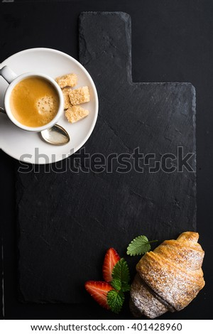 Espresso coffee cup and croissant with fresh strawberries on black  slate stone board over dark background. Top view, copy space - stock photo
