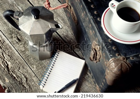 Espresso coffee, espresso maker and notepad on wooden surface - stock photo