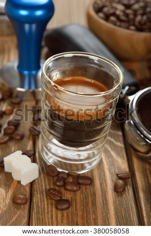 Espresso coffee in a glass cup on a brown background