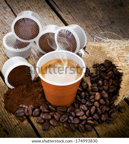 Espresso coffee in disposable cup with pods on wooden table - stock photo