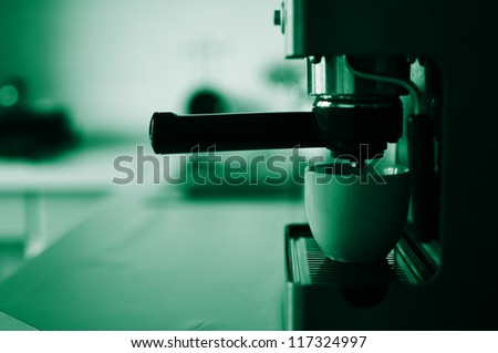 Espresso coffee machine with white ceramic cup on the kitchen.