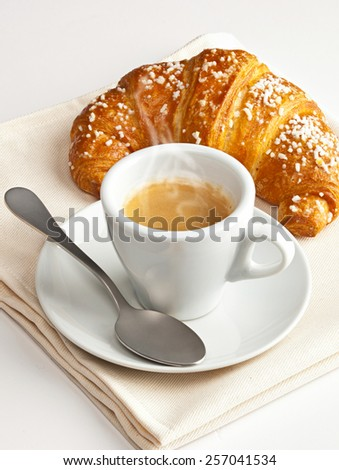Espresso coffee with croissant on beige towel. - stock photo