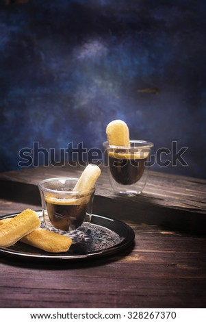 Espresso coffee with savoiardi cookies on wooden table. Toned image. Selective focus - stock photo