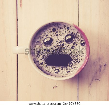 Espresso Cup with smiley face on wooden table, overhead view ,vintage color toned image - stock photo