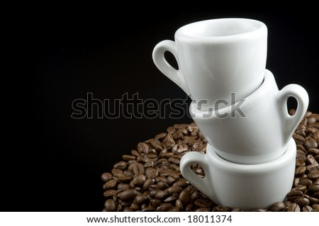 Espresso cups on coffee beans on a black background - stock photo