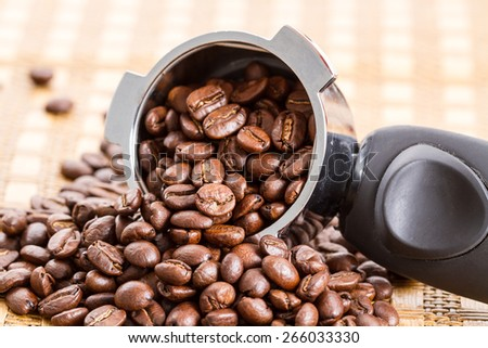 Espresso handle filled with coffee beans  - stock photo