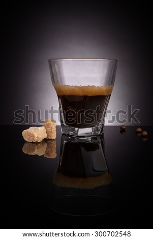 Espresso in glass with coffee beans and crane sugar cubes on dark background. Gourmet luxurious coffee drinking. - stock photo