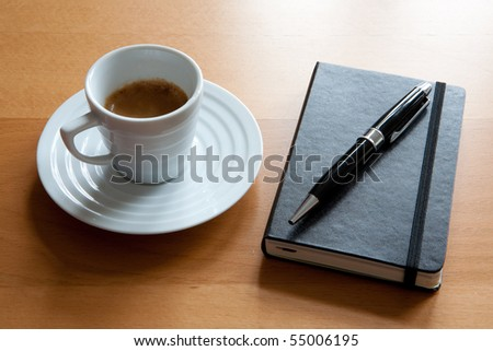 Espresso in white cup with Journal book and pen