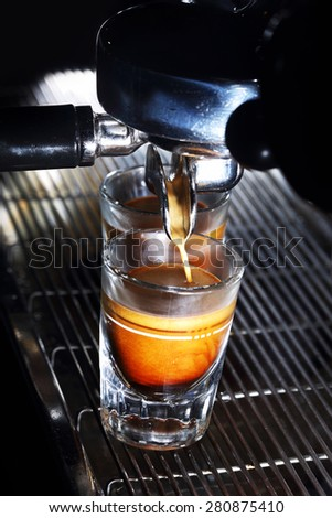 Espresso machine brewing a coffee. Coffee pouring into shot glasses. Toned image