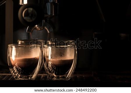 Espresso machine brewing a coffee, double wall glass. - stock photo