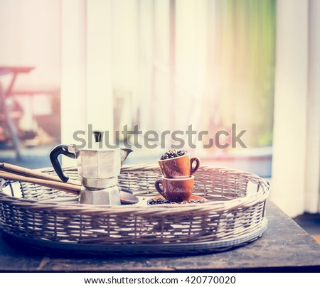 Espresso set with coffee cups, beans and coffee pot on sweet coffee on window sill  background - stock photo