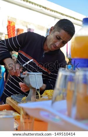 ESSAOUIRA - JULY 14: Unidentified man sells fresh orange juice in market of Essaouira, Morocco, July 14, 2013. Essaouira is one of the most popular tourist place on Atlantic coast in Morocco. - stock photo