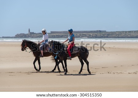 Essaouira, Morocco, Circa May 2013: People riding a horse on the Essaouira beach in Morocco