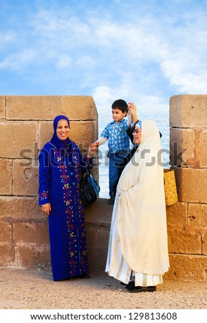 ESSAOUIRA, MOROCCO-DEC. 22: Local women wearing traditional robes in Essaouira, Morocco on Dec. 22, 2012. The historic walled fishing village dates back to the 16th century. - stock photo