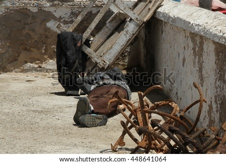 ESSAOUIRA, MOROCCO - JULY 4: A local fisherman asleep on the ground with rusty anchor hooks at his feet at the pier of the fishing port of Essaouira, Morocco on the 4th July, 2015.