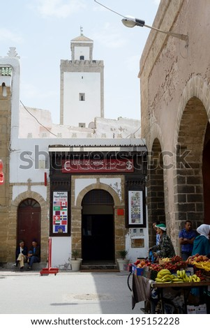 ESSAOUIRA, MOROCCO - MAY 12, 2014: Street scene showing bureau de change, fruit seller and mosque. Essaouira, Morocco. May 12, 2014. - stock photo