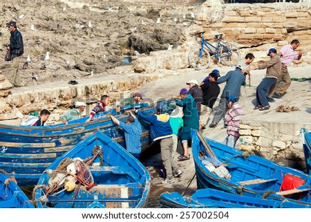 ESSAOUIRA, MOROCCO - NOVEMBER 26: Fishermen pushing a boat repair