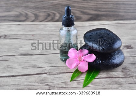 Essence oil and flower with zen stone on wood background - stock photo
