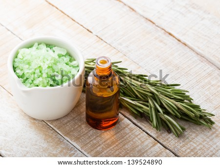 Essential aroma oil  and sea salt with rosemary on wooden background. Selective focus. - stock photo