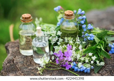 Essential aroma oil  in bottles on wooden background outdoor. Selective focus. Natural organic products. - stock photo
