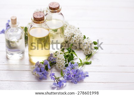 Essential aroma oil on  white painted wooden background. Selective focus. Place for text. - stock photo
