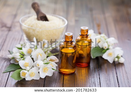 Essential aroma oil with jasmine  on wooden background. Selective focus.