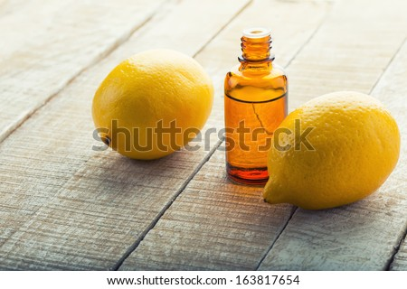 Essential aroma oil with lemon on wooden background. Selective focus. - stock photo