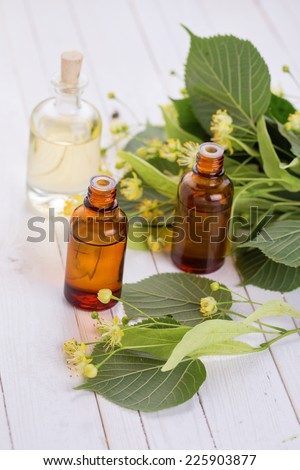 Essential aroma oil with linden  on wooden background. Selective focus.
