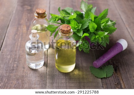 Essential aroma oil with mint on wooden background. Selective focus. - stock photo