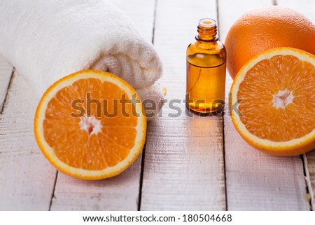Essential aroma oil with oranges on wooden background. Spa concept. Selective focus. - stock photo