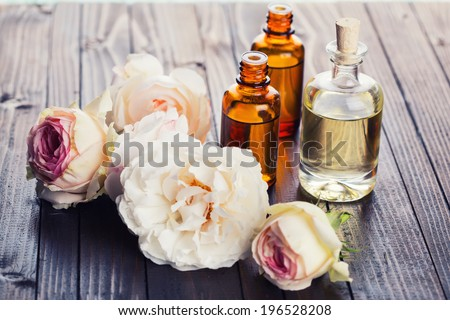 Essential aroma oil with roses on wooden background. Selective focus. - stock photo