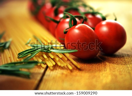 Essential Italian food ingredients. Shallow depth of field image of vine tomatoes, rosemary herb and dried pasta. Selective warm lighting. Copy space. - stock photo