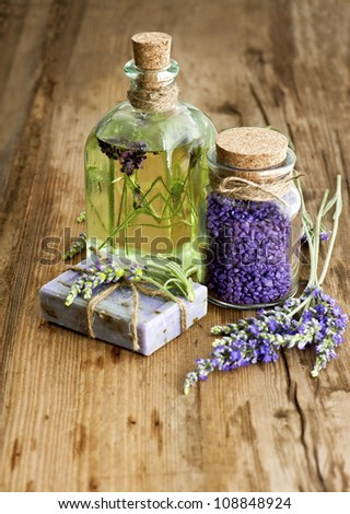 essential lavender oil, herbal soap and bath salt with fresh flowers on wooden background. selective focus