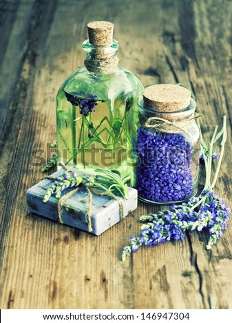 essential lavender oil, herbal soap and bath salt with fresh flowers on wooden background. retro style image. selective focus - stock photo