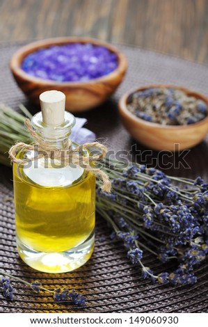 essential lavender oil with fresh flowers on wooden background - stock photo