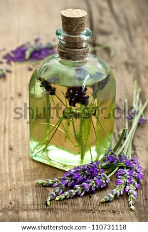 essential lavender oil with fresh flowers on wooden background. selective focus - stock photo