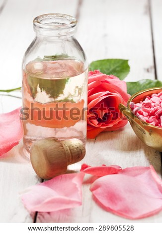 Essential oil and bath salt with rose petals on wooden background - stock photo